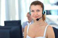 Business woman. Female customer support operator with headset and smiling Royalty Free Stock Photos
