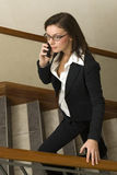 Business woman. Attractive brunette business woman wearing business suit using her cellphone Royalty Free Stock Photography
