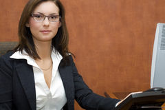 Business woman. Attractive brunette business woman wearing business suit at her desk Stock Image