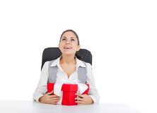 Business woman. Happy smile excited, sitting with red gift box, look up to empty copy space, isolated over white background Royalty Free Stock Photos