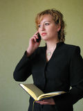 Business woman. Young beautiful girl talking on cellphone and holding open book in her hand Stock Image