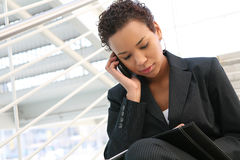 Business Woman. A pretty african american business woman at her company on the phone Stock Photos