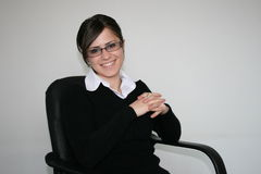 Business woman. Young business woman with glasses, sitting on a chair and smiling stock photography
