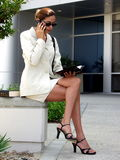 Business Woman 946. Business Woman Executive in suit with dayplanner and book talking on cell phone sitting in front of business offices Stock Images