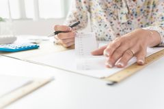 Business woman or accountant looking through the receipts. While working on a report Royalty Free Stock Photography