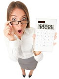 Business woman accountant shocked. Showing dollar signs on calculator. Surplus, debt or financial crisis concept image. Funny surprised young woman isolated on royalty free stock photography