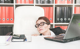 Business woman afraid. Business woman hiding behind table and afraid Stock Images