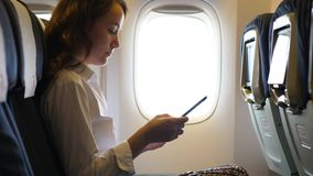Business woman in airliner texting in smartphone. Busy girl with mobile phone sitting in airplane alone against window stock footage