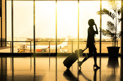 Business woman at Airport - Silhouette of a passenger. Business woman at Airport - The silhouette of the person has been modified to make her unrecognizable Royalty Free Stock Image