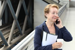 Business woman in the airport or train subway metro station making a phone call with smartphone Royalty Free Stock Image