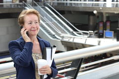 Business woman in the airport or train subway metro station making a phone call with smartphone Stock Images