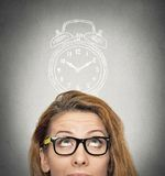 Business woman with alarm clock above her head. Closeup headshot young business woman with alarm clock drawing sketch above her head, isolated grey wall royalty free stock photos