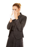 Business woman with an allergy or cold sneezing into tissue Stock Image