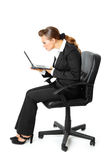 Business woman amazedly looks in laptops screen. Modern business woman sitting on  chair  and amazedly looks in laptops screen  isolated on white Royalty Free Stock Photography