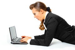 Business woman amazedly looks in laptops screen. Modern business woman laying on floor and amazedly looks in laptops screen isolated on white Stock Image