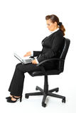 Business woman amazedly looks in laptops screen. Modern business woman sitting on chair  and amazedly looks in laptops screen  isolated on white Stock Photo