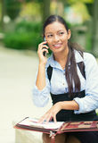 Business woman analyzing documents, talking on mobile phone Stock Photography