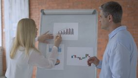 Business woman analyzing market data diagram. Close up of female marketer discussing market graph on white board. Marketing team working on marketing chart stock video footage