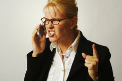 Business Woman Angry on the Ce. Business woman expresses her anger while on her cell phone Stock Photos