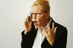 Business Woman Angry on the Ce. Business woman expresses her anger while on her cell phone Royalty Free Stock Photos