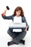 Business woman angry on her printer. Business woman in formal clothes angry on her printer and crushing it with hammer stock photo