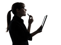 Business woman applying lipstick computer computing  digital tab Royalty Free Stock Photos