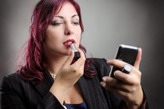Business woman applying makeup Royalty Free Stock Photography