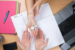 Business woman architect hand, handing over house key to customer. Stock Images