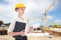 Business woman architect in yellow builder helmet. At construction site Stock Photography