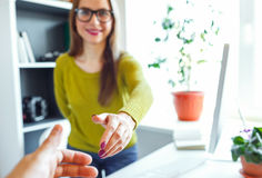 Business woman with arm extended to handshake Royalty Free Stock Image