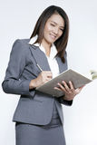 Business woman asian attractive standing using a pen writing dia. Business woman attractive young pretty in office standing enjoy using a pen writing diary note Stock Image