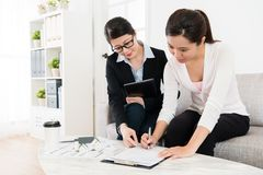 Business woman assisting client buying house. Smiling pretty business women assisting client buying house for family and young buyer signing contract deal to stock photo