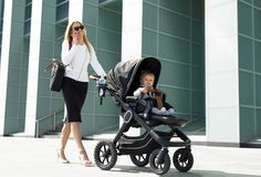 Business woman with baby carriage walking