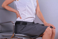 Business woman with back pain sitting in an office chair. Pain relief concept Royalty Free Stock Photography