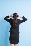 Business woman back to you. Back view of business woman think with isolated blue background Royalty Free Stock Photo