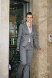 Business woman with bag on wheels exit elevator Royalty Free Stock Photography