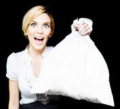 Business Woman Bagging A Bargain With Copyspace. Elated vivacious retail sales woman giving her endorsement holds up a blank white bag suitable for your Royalty Free Stock Image