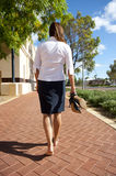 Business Woman Bare Feet. An attractive businesswoman is walking the pathway with her high heels shoes in one hand to give her sore feet a rest Royalty Free Stock Photo