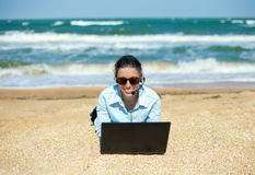 Business woman on the beach. Business woman talking using her laptop on the beach royalty free stock photos