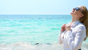 Business woman on the beach. she enjoys the view of the sea. she unbuttoned her shirt and breathes in the sea air stock photography