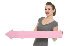 Business woman with big arrow pointing in corner Royalty Free Stock Photo