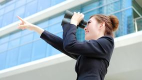 Business woman with binocular. Looking forward with office building Stock Images