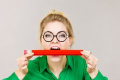 Business woman biting pencil. Funny crazy business woman wearing eyeglasses biting pencil. Studio shot on grey background stock image