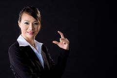 Business woman in black. Business woman with hand gesture on black background Royalty Free Stock Image