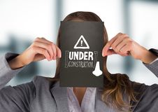 Business woman with black card over face showing white construction doodle against blurry grey offic Stock Photos