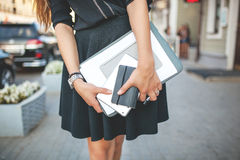 Business woman in black dress in the city with documents Royalty Free Stock Image