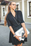 Business woman in black dress in the city with documents Royalty Free Stock Photography