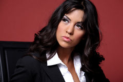 Business-woman in black suit. Young beautiful Latino business-woman in black suit posing on red background Stock Photo