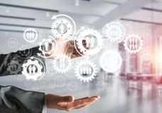 Cogwheels and gears mechanism as social communication concept. Business woman in black suit keeping white social gear icons in hands with office view and Stock Photo