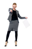 Business woman with a blank sheet of paper. Girl in full growth points at the camera Royalty Free Stock Photography